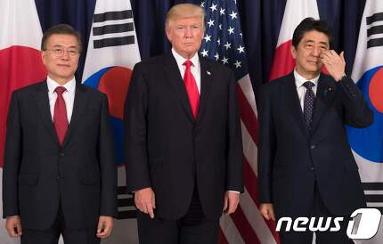 문재인 대통령(왼쪽)과 도널드 트럼프 미국 대통령, 아베 신조 일본 총리가 6일 오후(현지시간) G20 정상회의가 열리는 독일 함부르크 시내 미국총영사관에서 열린 한미일 정상만찬에서 기념촬영을 하고 있다.  © AFP=뉴스1
