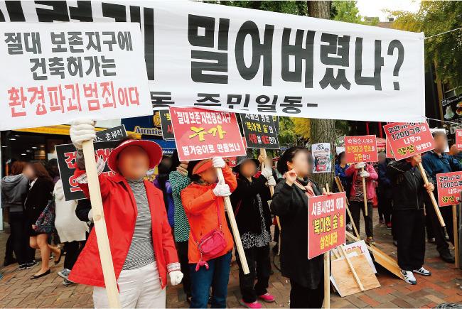 2014년 10월 서울 서대문구 이화여대 정문 앞에서 인근 주민들이 북아현동 이화여대 기숙사 건립 중단을 요구하고 있다.[뉴스1]