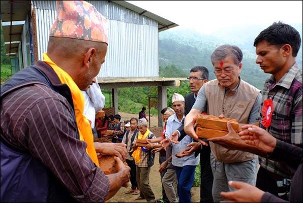 지난해 6월 네팔을 방문한 문재인 대통령(오른쪽에서 두 번째)이 현지인들과 줄지어 서서 벽돌을 나르고 있다. 사진은 당시 안내를 맡은 박타 람 라미차네 씨의 페이스북 사진.