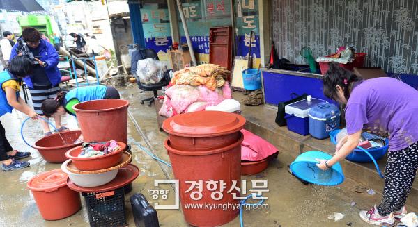 17일 오후 충북 청주시 흥덕구 복대동 주택가에서 주민과 자원봉사자들이 전날 내린 폭우로 침수됐던 가재도구 등을 꺼내 물로 씻고 있다.  청주 | 정지윤 기자 color@kyunghyang.com