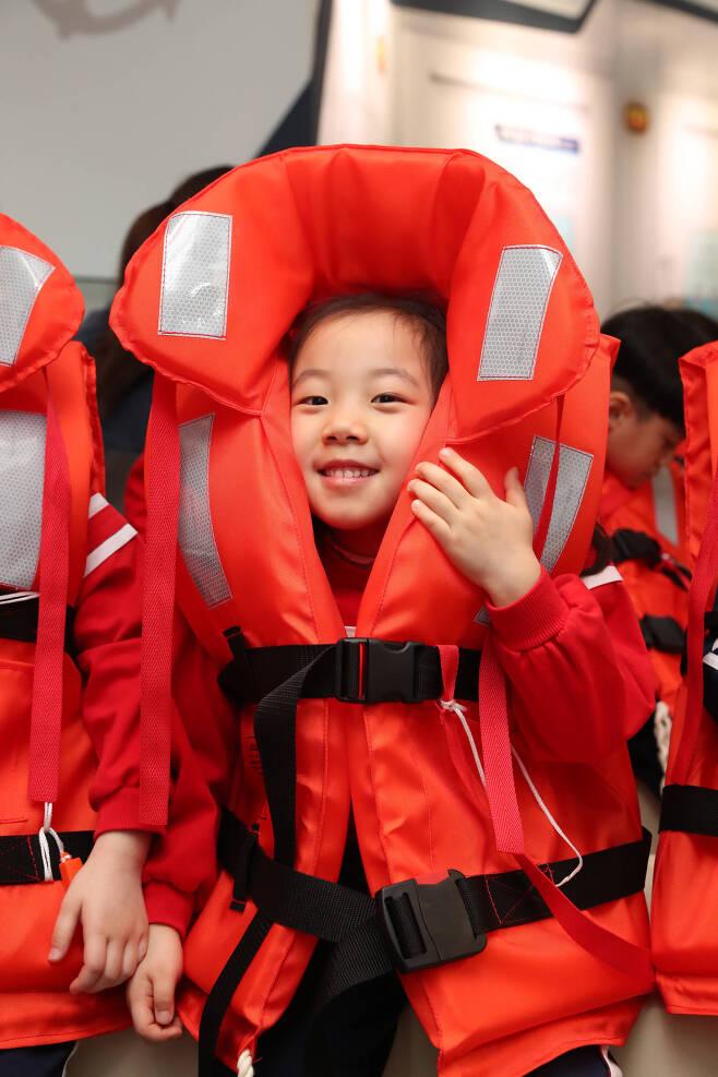 자기 키보다 큰 구명 조끼를 착용한 어린이가 재미난 듯 웃음짓고 있다. 우상조 기자