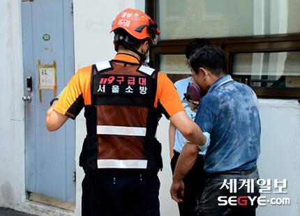 서울 낮 최고 기온이 35도까지 치솟는 등 폭염 특보가 내려진 지난 20일오후 서울 도심 속 화재현장에서 한 구조대원이 연기를 마신 용단 작업자를 이송하고 있다.