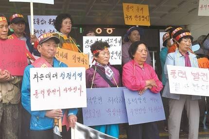 지난 21일 경북 청송군청 앞에서 열린 풍력발전 반대 기자회견에서 주민들이 팻말을 들고 있다. 이상돈 의원실 제공
