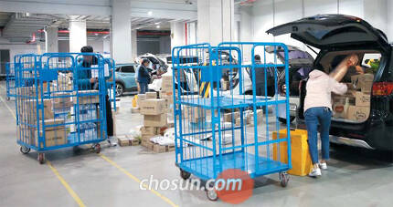 지난달 31일 서울시 송파구 쿠팡 물류센터에서 일반인 단기 배달원들이 자신의 차량에 택배 박스를 싣고 있다. 쿠팡에 따르면 서비스 개시 두 달 만에 일반인 택배 기사 신청자가 9만4000명을 넘어섰다. /김연정 객원기자