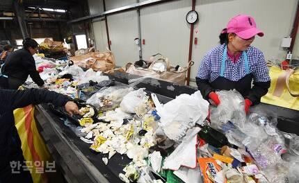 15일 인천 남동구 재활용품 선별장 현대자원 직원들이 컨베이어벨트 위의 재활용품 폐기물 가운데서 페트병 등 재활용 가치가 있는 자원을 골라 내고 있는 한편 최동철(사진 왼쪽) 대표가 재활용이 되지 않는 음식물 등이 뒤섞인 쓰레기를 가리키고 있다. 배우한 기자