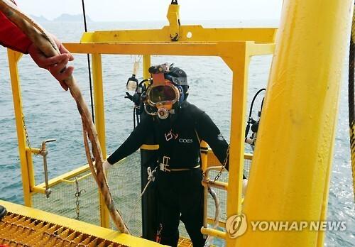 지난 19일 상하이샐비지 컨소시엄 소속 1만1천706t 크레인 작업선 다리(大力)호에서 중국인 잠수사가 다이빙 케이스에 탑승해 잠수하고 있다. (연합뉴스 자료사진)