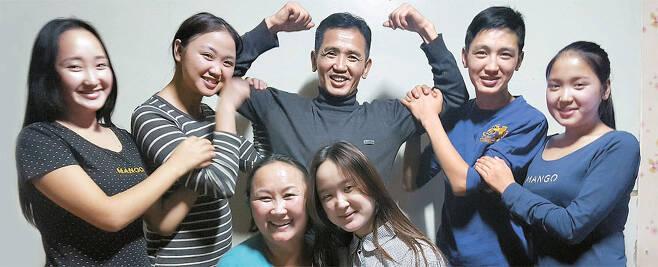 <b>몽골 '영웅엄마 2호' 훈장 가족</b> 몽골 울란바토르 바양걸구(區)의 단독주택에 사는 에네비스(45·뒷줄 가운데)· 오간치멕(40·여·앞줄 왼쪽) 부부와 자녀들. 몽골은 아이 4명을 낳으면 '영웅엄마 2호' 훈장을 수여한다. 아들 하나, 딸 넷을 낳은 오간치멕은 27세 때 훈장을 받았다. [울란바토르(몽골)=노진호 기자]
