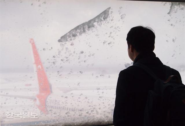 24일 출발 예정된 모든 항공편이 결항된 제주국제공항에서 한 승객이 눈 덮인 활주로를 바라보고 있다. 제주=김형준기자