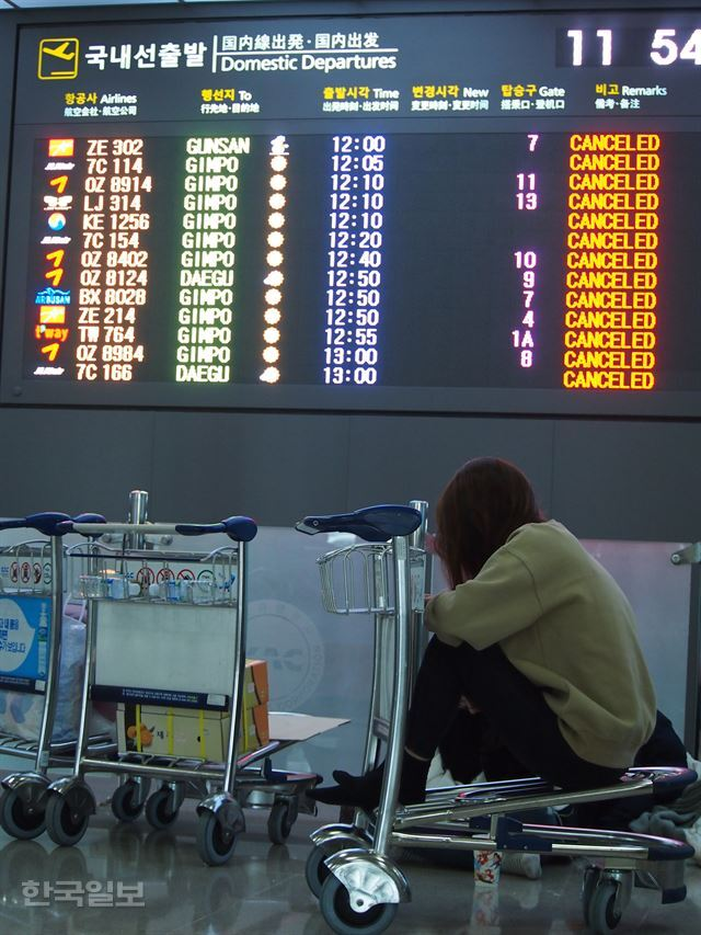 24일 출발 예정된 모든 항공편이 결항된 제주국제공항에서 한 승객이 이동 카트에 앉아 있다.