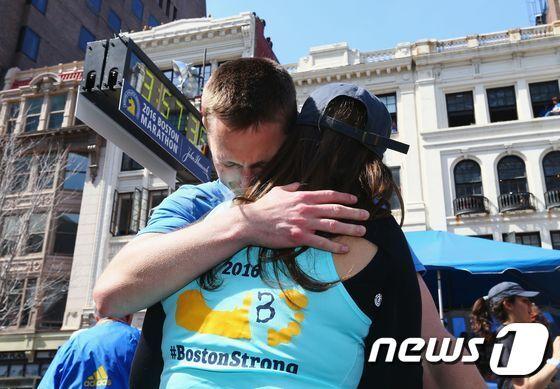 패트릭 다운즈가 보스턴 마라톤대회 결승선을 통과한 후 아내를 끌어안고 있다. © AFP=뉴스1