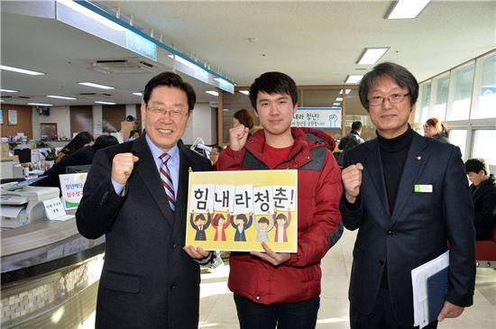 이재명 성남시장(왼쪽)이 청년배당 수령을 위해 동 주민센터를 찾은 청년과 함께 화이팅을 외치고 있다.