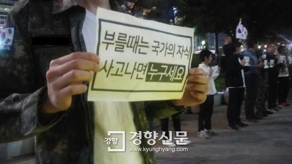 14일 밤 서울 종로구 동아일보사 앞에서 열린'예비군과 병사 처우개선을 요구하는 집회'에 참가한 한 남성이 손팻말을 들고 있다. / 김원진 기자