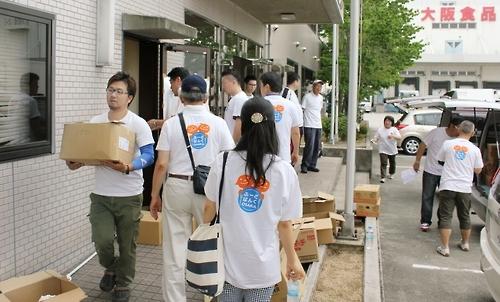 [사카이<일 오사카부> 교도=연합뉴스 자료사진] 오사카부 사카이시에 있는 오사카식품유통센터에 있는 재고식품을 아동양호시설 등지에 배급해주기 위해 식품을 나르는 자원봉사자들.