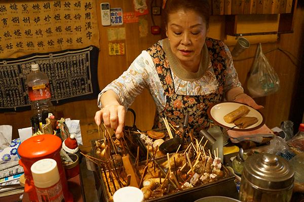 시즈오카에서만 맛볼 수 있는 쿠로오뎅을 건네주는 선술집 주인. ⓒ MK스타일 / 월간여행스케치