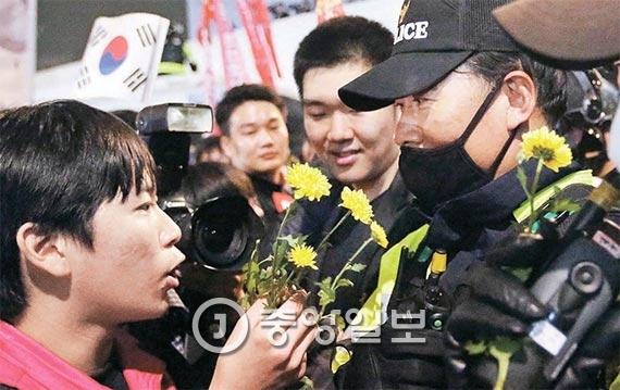 청와대 입구인 서울 내자동에서 한 학생이 경찰에게 꽃을 건네고 있다. [사진 박종근 기자]