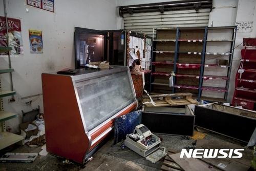 【치우다드 볼리바르(베네수엘라)= AP/뉴시스】 = 19일(현지시간)  베네수엘라의 치우다드 볼리바르 시내에 있는 한 식료품점 내부가 약탈 당한 채 텅 비어 있는 광경.  니콜라스 마두로 대통령이 지난 주 가장 유통량이 많은 100볼리바르 지폐를 폐지하고 고액권 발행을 선언한 이후로  은행앞에 화폐를 바꾸려는 군중이 몰리고 식료품과 휘발유등 생필품 구매가 불가능해지면서 여러 도시에서 폭동과 약탈이 발생했다.