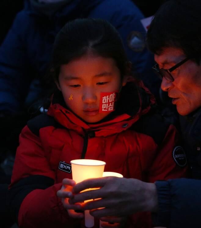 박근혜정권퇴진비상국민행동이 4일 저녁 서울 광화문광장에서 연 14차 촛불집회에 할아버지와 함께 참가한 어린이가 촛불을 들고 있다. 이정우 선임기자 woo@hani.co.kr