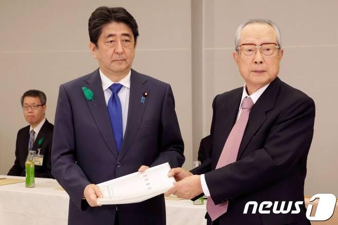 일왕 생전퇴위 문제 논의를 위한 '전문가 회의'의 타카시 이마이 의장이 21일 아베 신조(安倍晋三) 일본 총리에게 최종 보고서를 전달하고 있다. © AFP=뉴스1