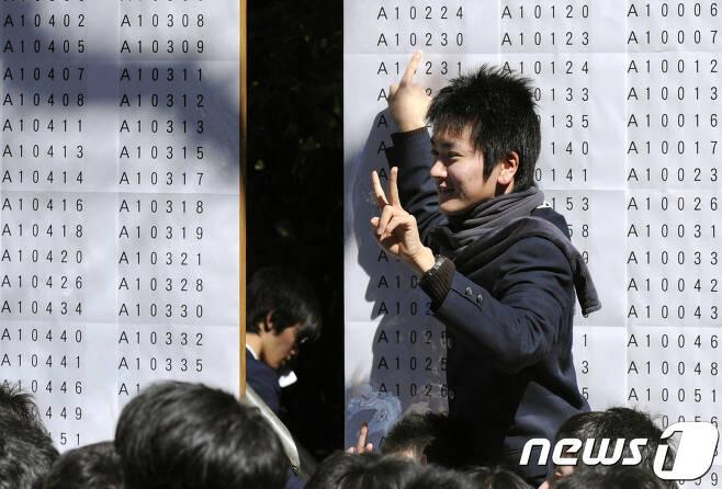 일본 도쿄대 앞에서 한 수험생이 대학 합격 여부를 확인하고 기뻐하고 있다. © AFP=뉴스1