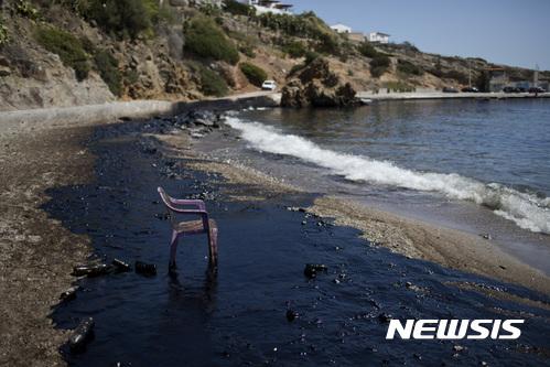 【아테네( 그리스) = AP/뉴시스】 = 아테네에서 가까운 살라미나섬 해안이 기름으로 오염된 채 플래스틱 의자 하나만 서 있다. 소형 유조선 한 척이 10일 침몰해 기름이 유출되고 있다며 그리스 당국은 이 일대 모든 해수욕장의 해수욕객들에게 대피령을 내렸다.