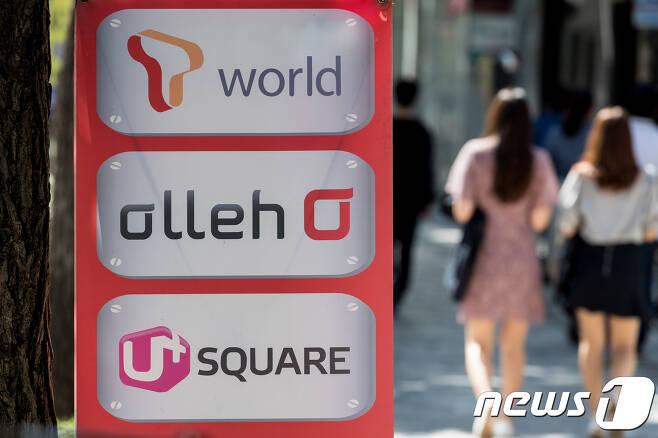 서울 시내 한 이동통신 판매점 앞을 시민들이 지나고 있다./뉴스1 © News1