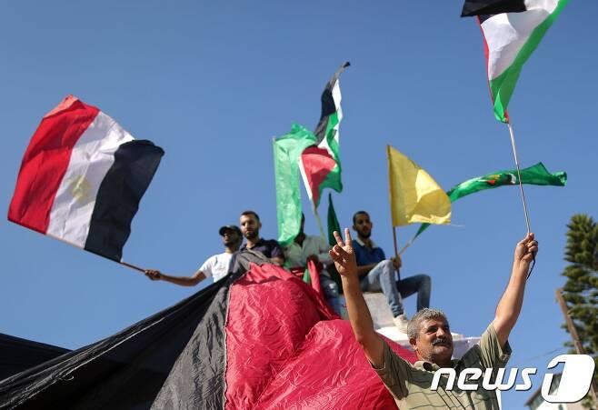 팔레스타인 주민들이 12일(현지시간) 이집트와 팔레스타인·파타·하마스를 상징하는 깃발을 흔들며 통합합의문에 환호하고 있다. © AFP=뉴스1