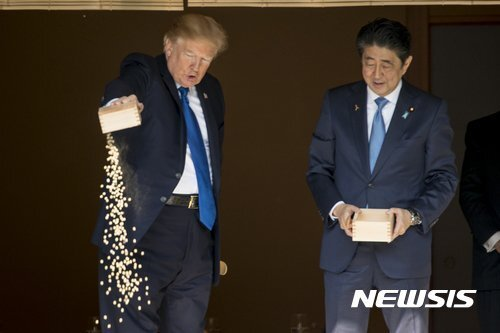 잉어 밥 쏟아붓는 트럼프. 트럼프 이전 아베 총리가 먼저 잉어 밥을 쏟아부어 밥이 든 상자가 비어있다(오른쪽)/사진=AP,뉴시스