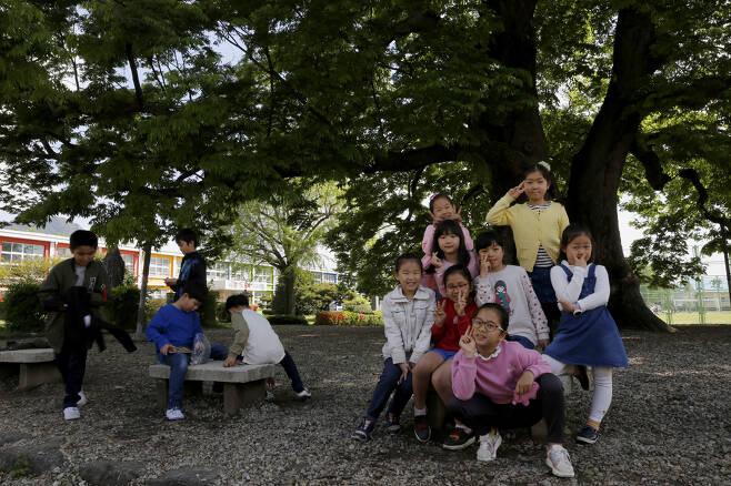 느티나무 숲그늘에 모여서 노는 초등학생들 모습. 사진기를 본 여학생들이 사진을 찍어달라며 졸랐다. ⓒ이돈삼