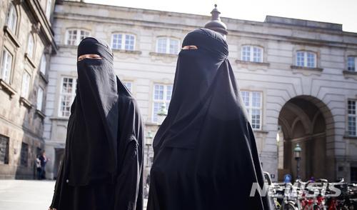 【코펜하겐=AP/뉴시스】 덴마크 의회가 니캅과 부르카 등 이슬람 베일 착용을 금지하기로 결정한 31일 당일 니캅을 쓴 두 여성이 의사당 앞을 지나가고 있다. 2018. 5. 31.