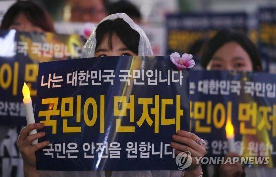 30일 오후 서울 종로구 동화면세점 앞에서 열린 난민법과 무사증(무비자) 제도 폐지 집회에서 참가자들이 손팻말을 들고 있다.사진=연합뉴스
