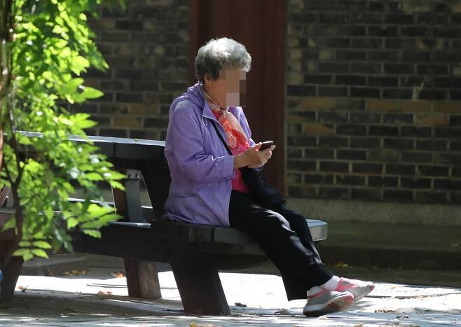 30일 오전 서울 한 공원에서 노인이 휴대폰을 들여다보고 있다. 신소영 기자 viator@hani.co.kr