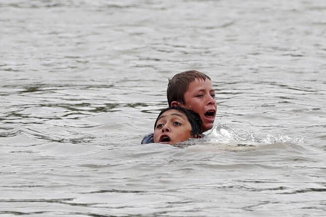 국경을 넘기 위해 수치아떼강을 헤엄치는 온두라스 이민자들.  EPA/=연합뉴스