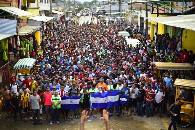 멕시코에 입국하려는 온두라스 출신 이민자들이 20일(현지시간) 국경지대에서 대규모 시위를 벌이고 있다.  AFP=연합뉴스