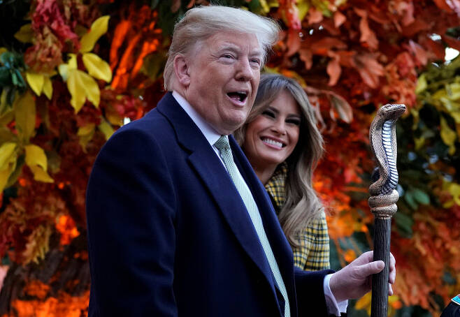 도널드 트럼프 미국 대통령과 멜라니아 여사가 28일(현지시간) 백악관에서 열린 핼러윈 행사에서 웃고 있다. 워싱턴|로이터연합뉴스