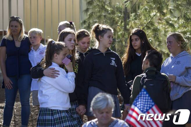 7일(현지시간) 미국 로스앤젤레스 총기난사 사건으로 숨진 보안관보 론 힐러스의 시신을 실은 차를 지켜보며 슬퍼하는 학생들. © AFP=뉴스1
