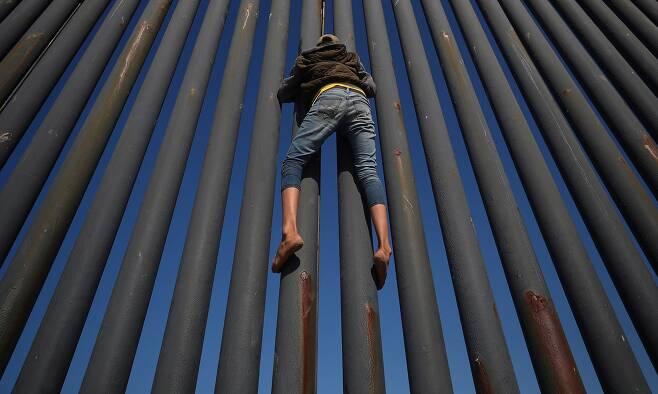 한 이민자가 18일(현지시간) 멕시코 북부 티후아나의 미국-멕시코 국경 담장을 오르고 있다. [로이터=연합뉴스]