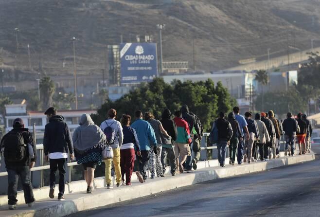 캐러밴 이민자들이 17일(현지시간) 멕시코 티후아나에 도착해 미국-멕시코 국경으로 이동하고 있다. [AFP=연합뉴스]