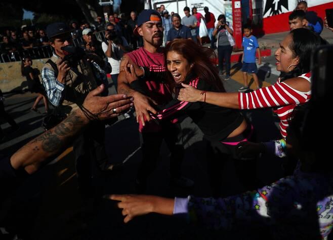 멕시코 티후아나 주민들이 18일(현지시간) 이민자들과 충돌하고 있다. [로이터=연합뉴스]