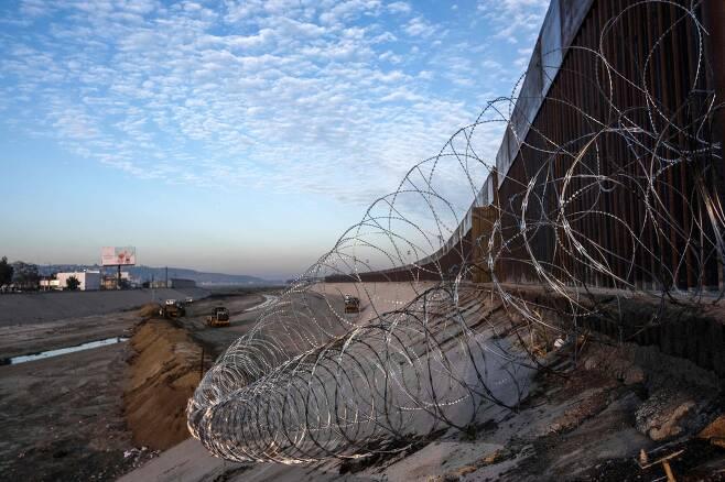 미국 당국이 18일(현지시간) 캐러밴 이민자들에게 대응하기위해 미국-멕시코 국경지역인 티후아나 강에 에 모래 언덕과 가시 철망을 설치하고 있다. [AFP=연합뉴스]