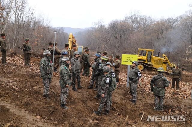 【서울=뉴시스】 국방부는 22일 남북군사당국이 '판문점선언 이행을 위한 군사분야 합의서'(9.19.)에 따라 공동유해발굴의 원활한 추진을 위해 강원도 철원 '화살머리고지' 일대에서 남북 도로개설을 추진하고 있는 가운데, 도로연결 작업에 참여한 남북인원들이 MDL인근에서 상호 조우하는 모습의 사진을 공개했다. 2018.11.22. (사진=국방부 제공) photo@newsis.com