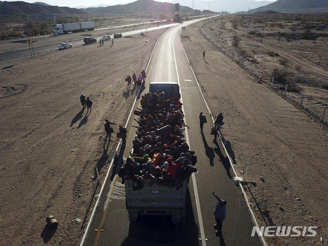 【멕시칼리=AP/뉴시스】중미 출신 불법 이주민들이 20일(현지시간)멕시코 멕시칼리에서 트럭을 얻어타고 미국 접경도시 티후아나로 향하고 있다. 2018.11.21