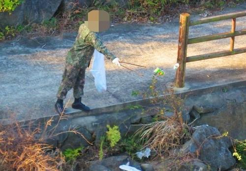 환경정화활동 중 강정천에 쓰레기 버리는 해군 [해군기지 반대주민회 제공]