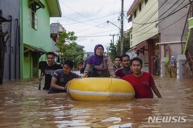 【마카사르=AP/뉴시스】23일(현지시간) 인도네시아 남술라웨시 마카사르에 홍수가 나 한 여성이 고무보트를 타고 주민들의 도움으로 대피하고 있다. 이번 폭우로 댐이 넘치고 산사태가 발생해 최소 6명이 숨지고 2000명 이상의 이재민이 발생했다고 현지 관계자가 밝혔다. 2019.01.23.