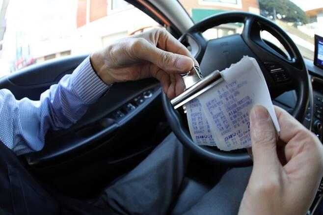 택시요금 정산 계산서를 살펴보는 이충신 기자. 사진 정용일기자