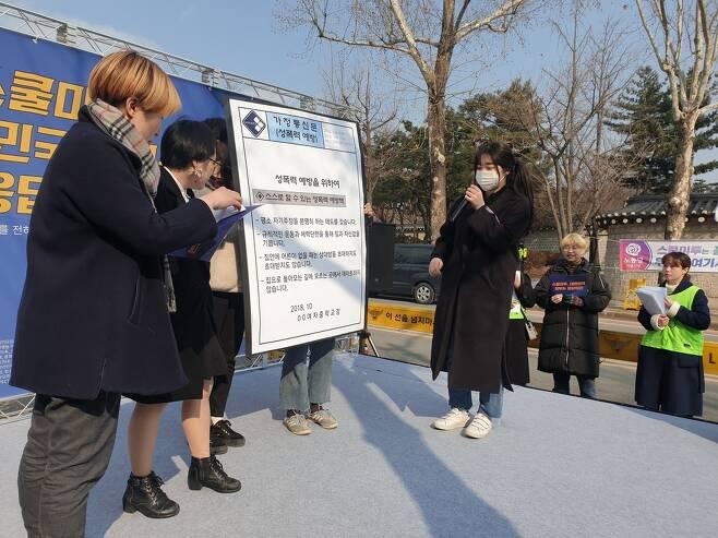 성폭력을 피해자의 책임으로 돌리는 실제 가정통신문 내용을 가져와 소개하는 참가자들.