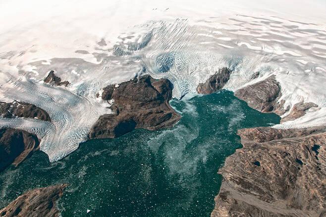 NASA 항공기가 촬영한 그린란드 남부 피오르에서 빙하가 흘러내려가고 있는 모습(2016년 9월2일). 미국항공우주국(NASA)