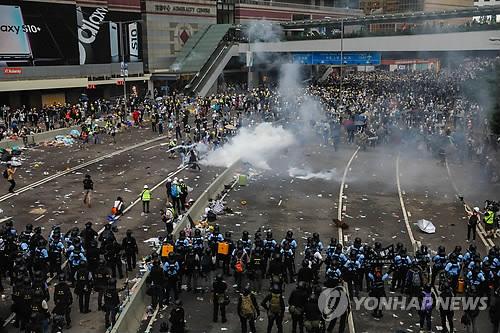 최루탄 발사하며 시위대 해산 시도하는 홍콩 경찰 (홍콩 AFP=연합뉴스) 12일 홍콩 정부청사 건물 주변에서 경찰이 '범죄인 인도 법안'에 반대하는 시위대를 향해 최루탄을 발사하며 해산을 시도하고 있다. leekm@yna.co.kr