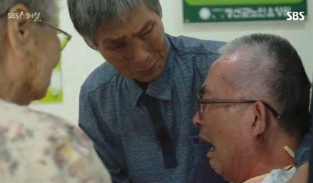 """정연관 상병 가족과 15년 만에 만난 김용현씨. 정 상병 어머니가 김씨를 보며 """"이 사람아, 이 사람아 왜 이렇게 됐어""""라며 안타까워했다. SBS 스페셜 캡처"""