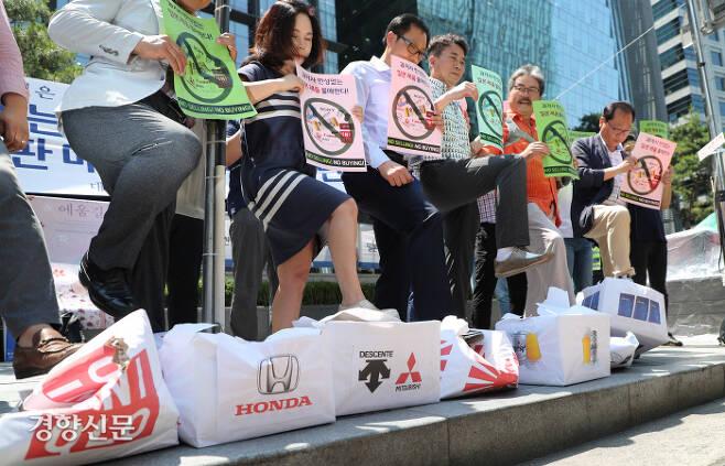 """자영업자들 """"유니클로·혼다·데상트 등 일본 제품 안 팔아요"""" 일본 제품 불매와 판매 중지 뜻을 밝힌 한국중소상인자영업자총연합회 회원들이 5일 서울 종로구 옛 주한 일본대사관 앞에서 일본 제품 브랜드가 인쇄된 종이박스를 발로 짓뭉개는 퍼포먼스를 진행하고 있다.  김영민 기자 viola@kyunghyang.com"""