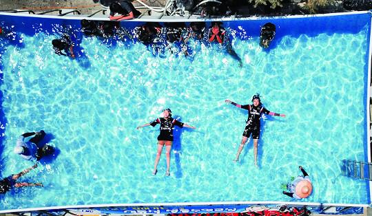 삼성초등학교에서 학생들이 생존수영의 최종 단계인 '누워뜨기'를 하고 있다. 몸에 힘을 빼고 손과 발을 벌린 채 누워 물에 떠 있는 방법이다.